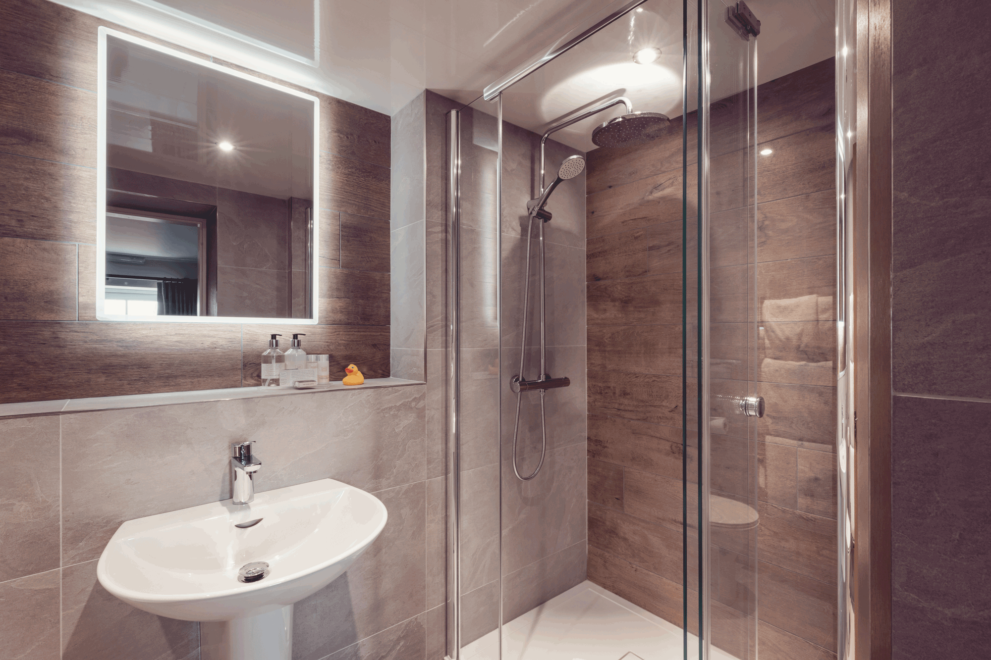 cubicle shower with white sink and large mirror with back light