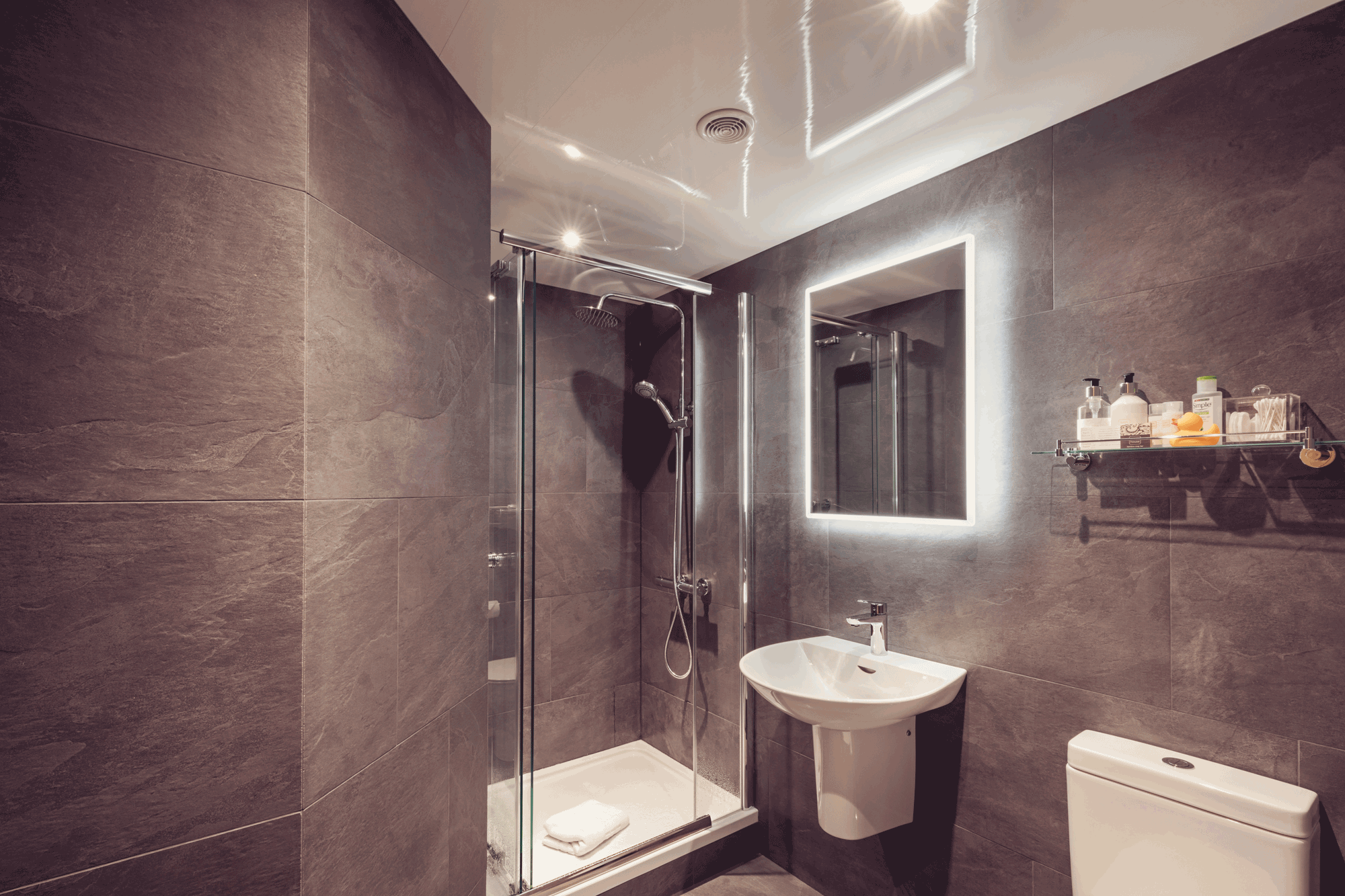 corner shower with white sink and large mirror with back light