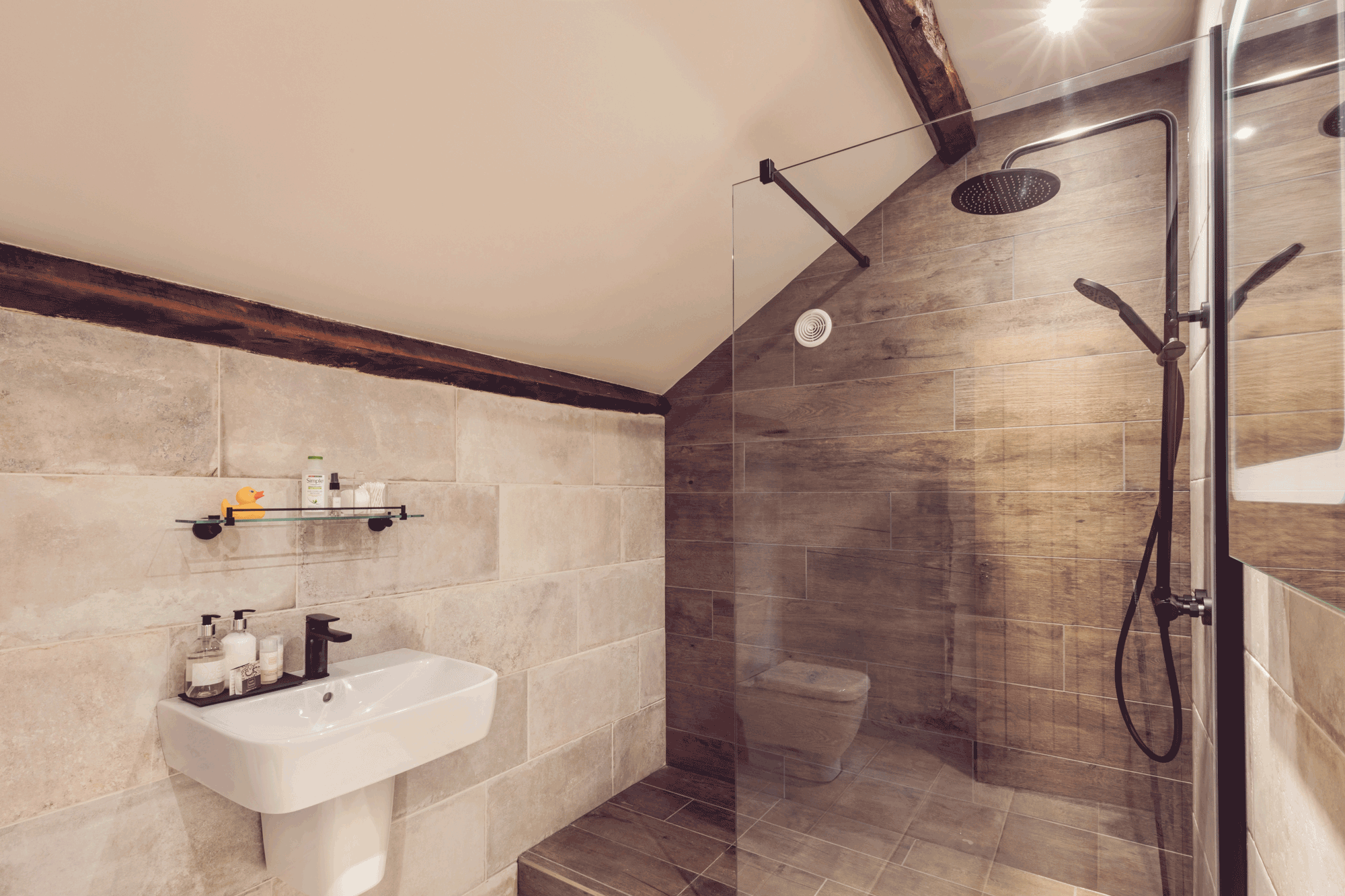 arge walk in shower, white sink, pale grey tiles and an oak beam