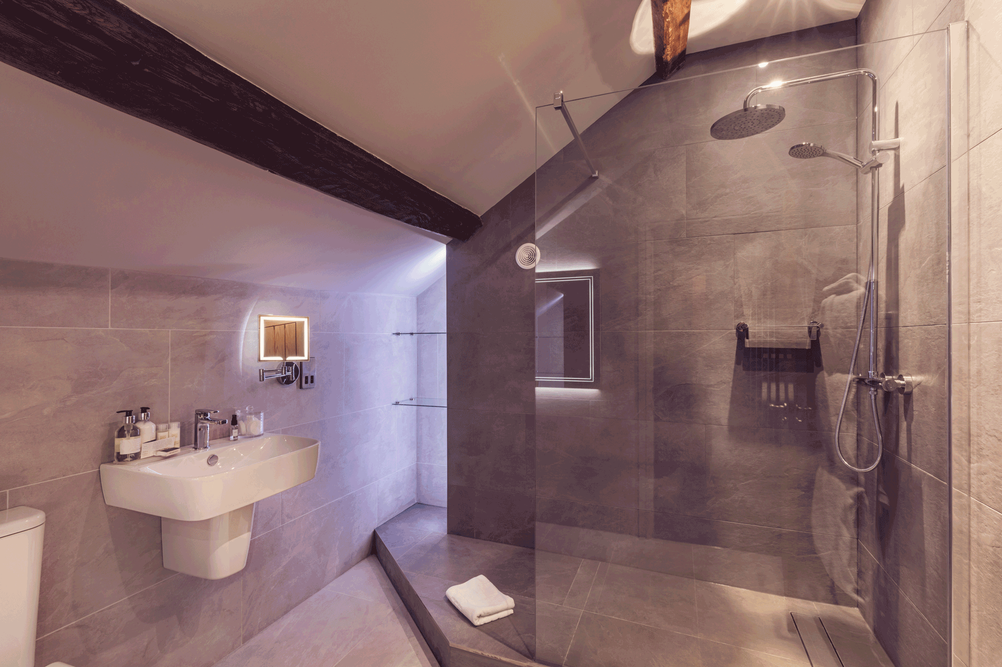 large walk in shower, white sink, pale grey tiles and an oak beam